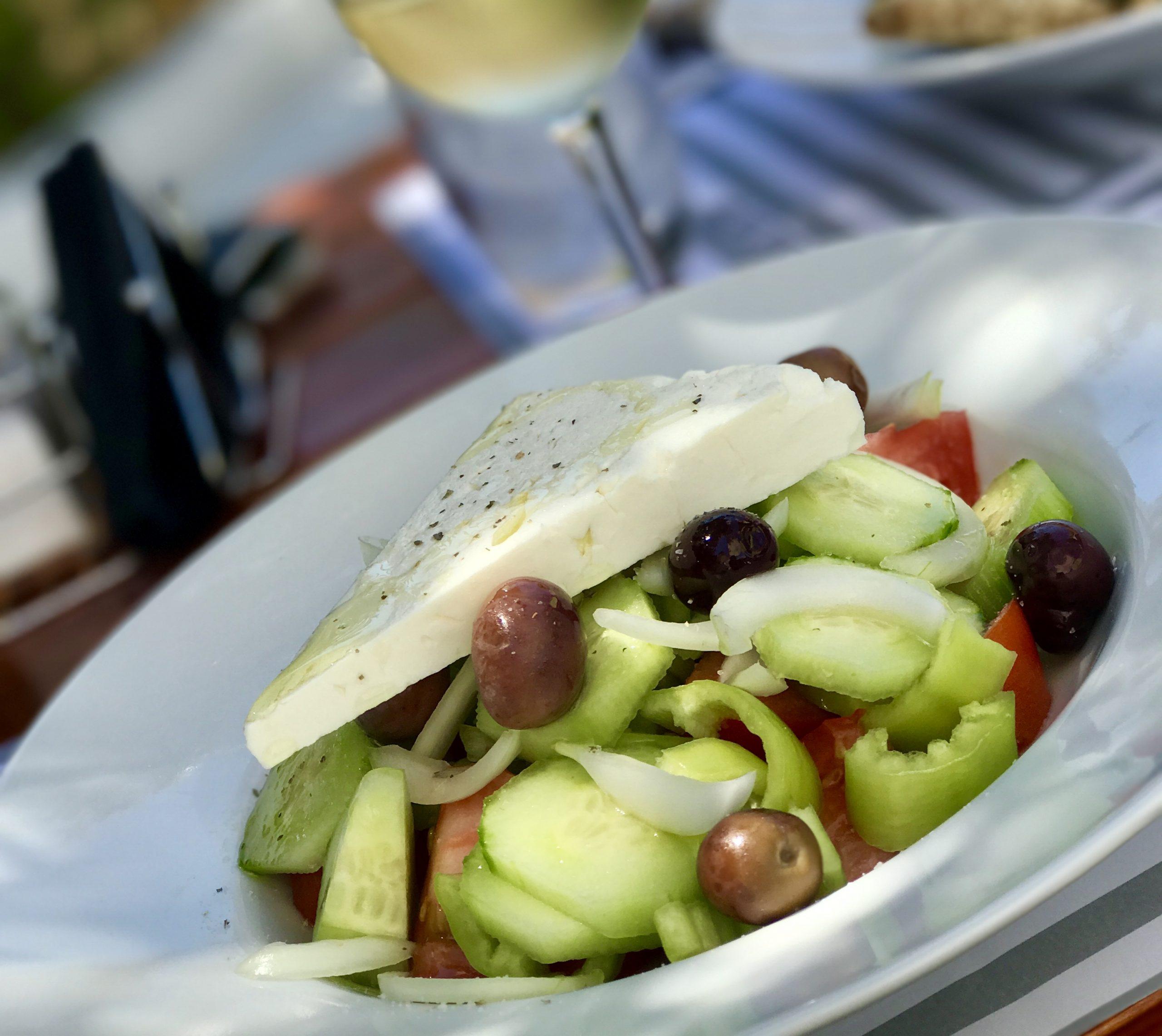 Bilden visar en grekisk sallad med en stor fetaostbit och svarta oliver på toppen
