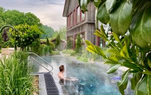 På bilden badar en man i den stora utomhuspoolen som håller 39 grader. Utomhuspoolen är en del av Sinnenas spa och spaträdgården på Ästad vingård i Halland