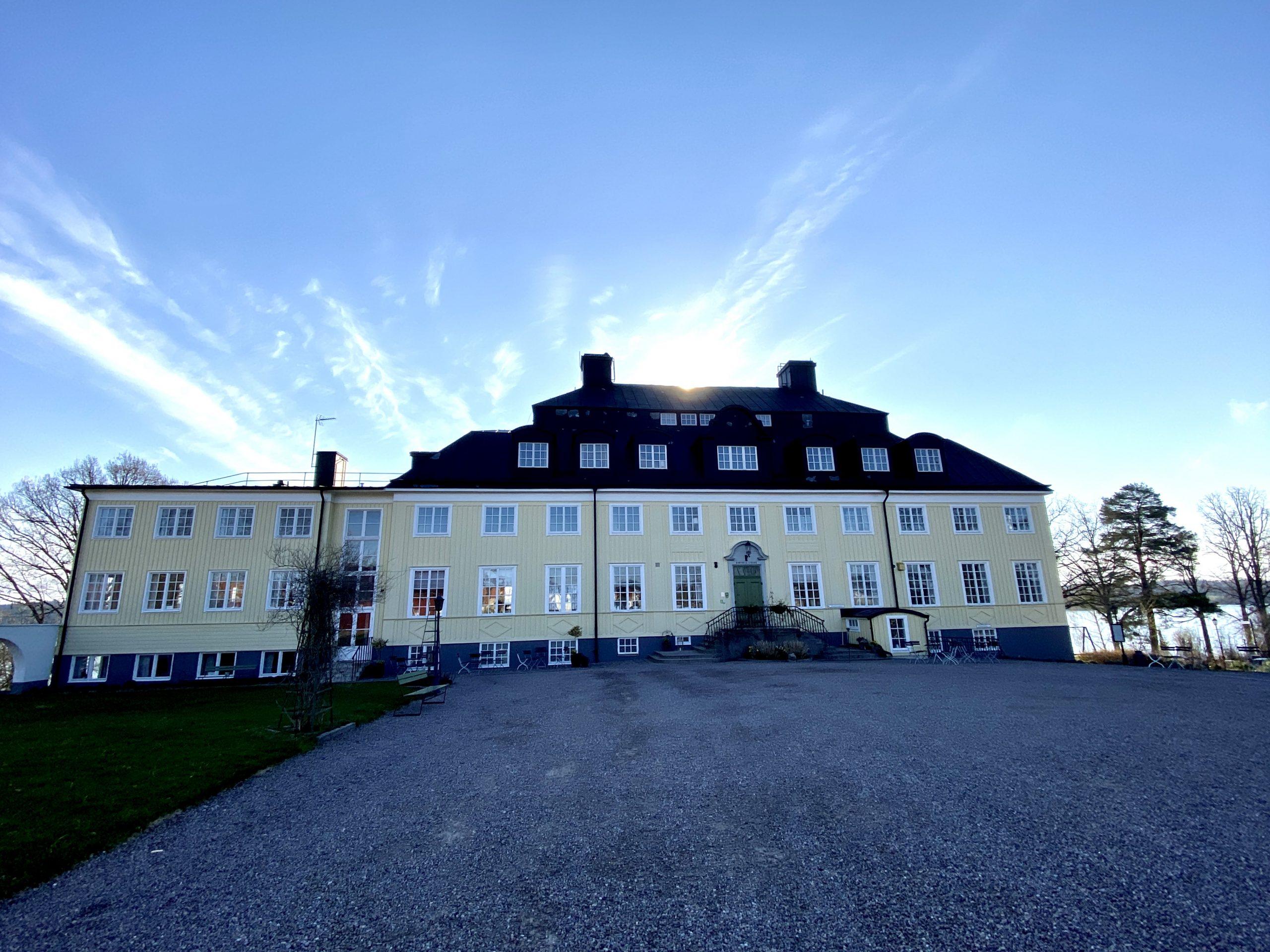 Bilden visar Rimforsa strand. En gul herrgårdsliknande hotellbyggnad i Rimforsa vid sjön Åsunden i Östergötland